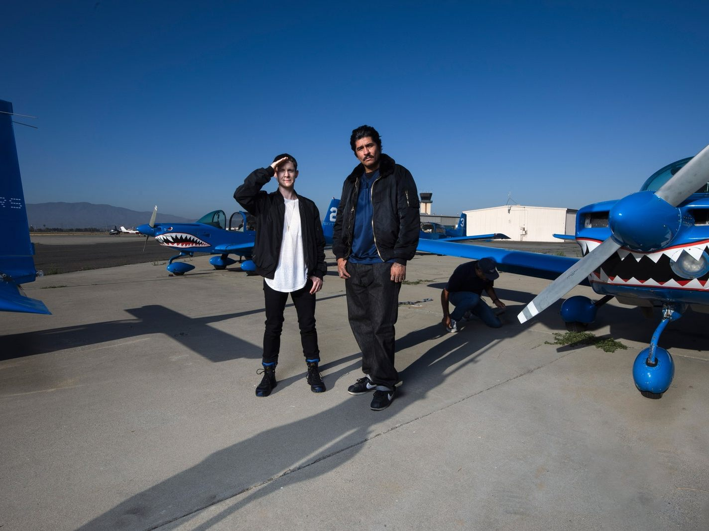 Rafa Esparza and Cassils stand in front of a plane