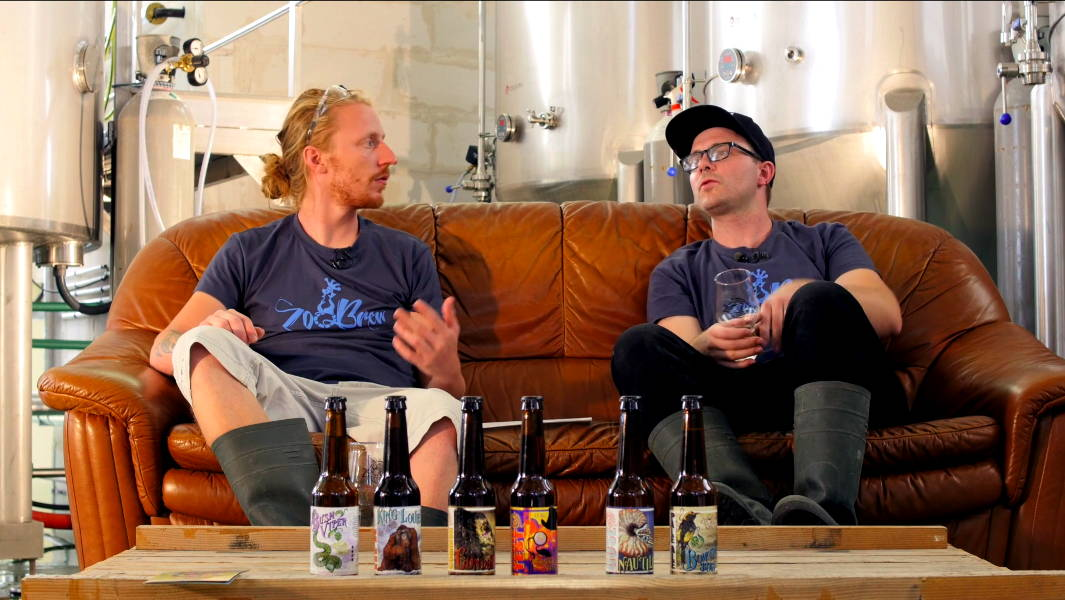 Two men sitting on a couch with beer tanks and beer bottles