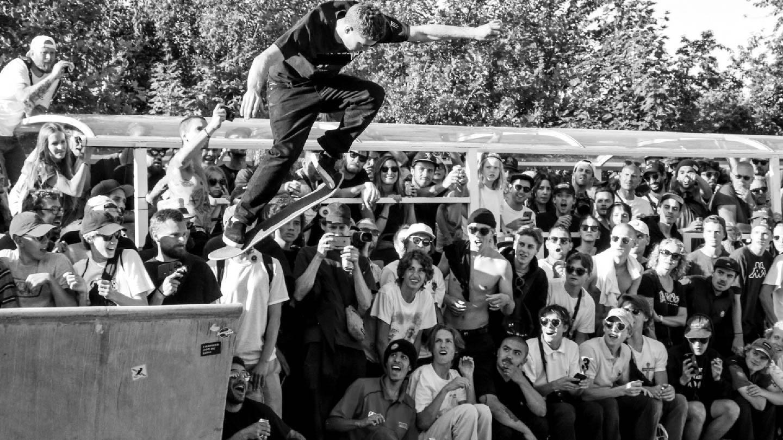 Photo d'un skateboarder qui replaque un treflip sur des marches avec son skateboard sous les pieds, il y a du public dans la street et des photographes pour le contest.