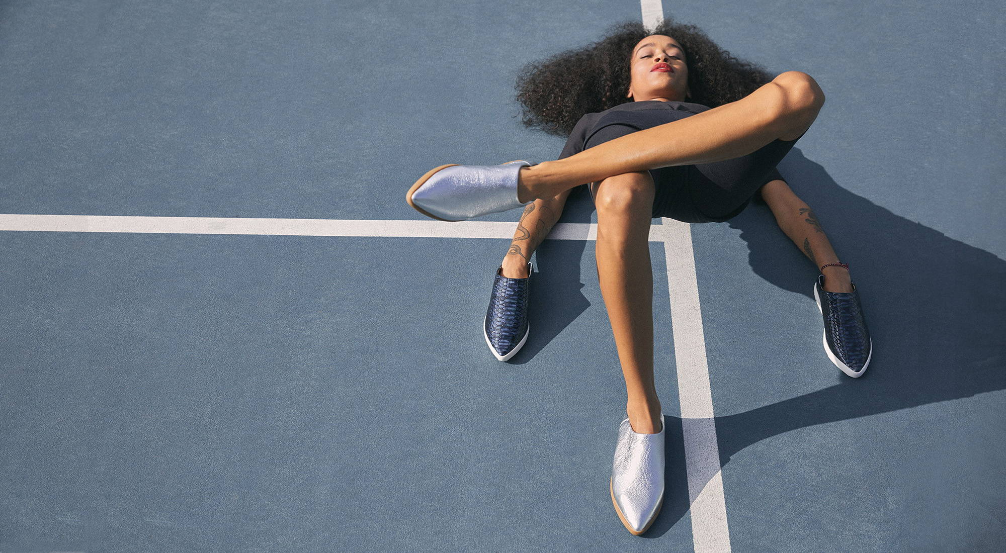 Woman laying on tennis court with shoes