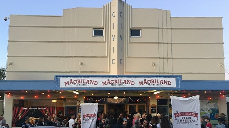 An art-deco style cinema exterior with Maorliand Film Festival banners.