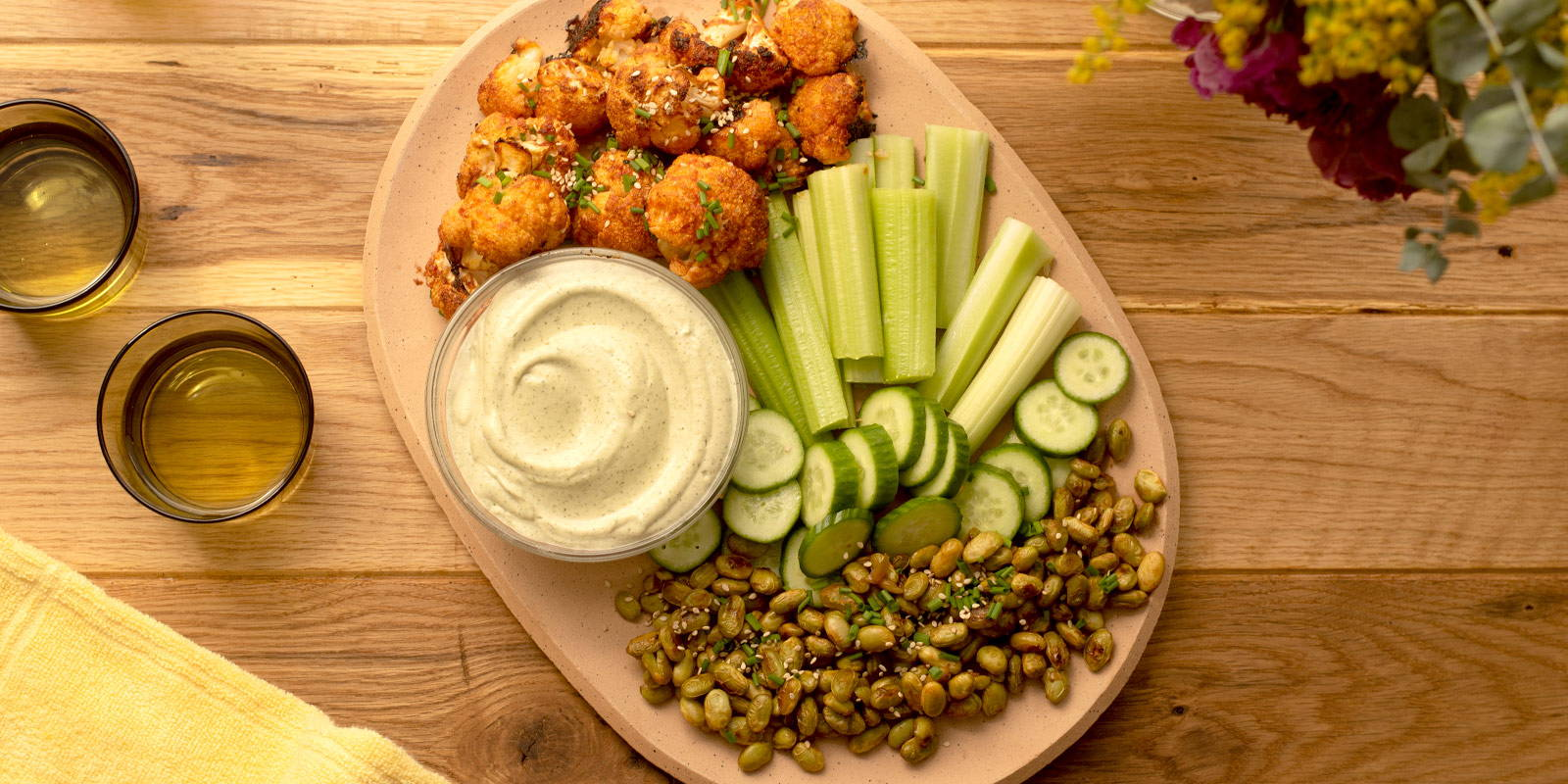 Wooden platter with cauliflower wings, edamame, cashew ranch, celery, and cucumbers.