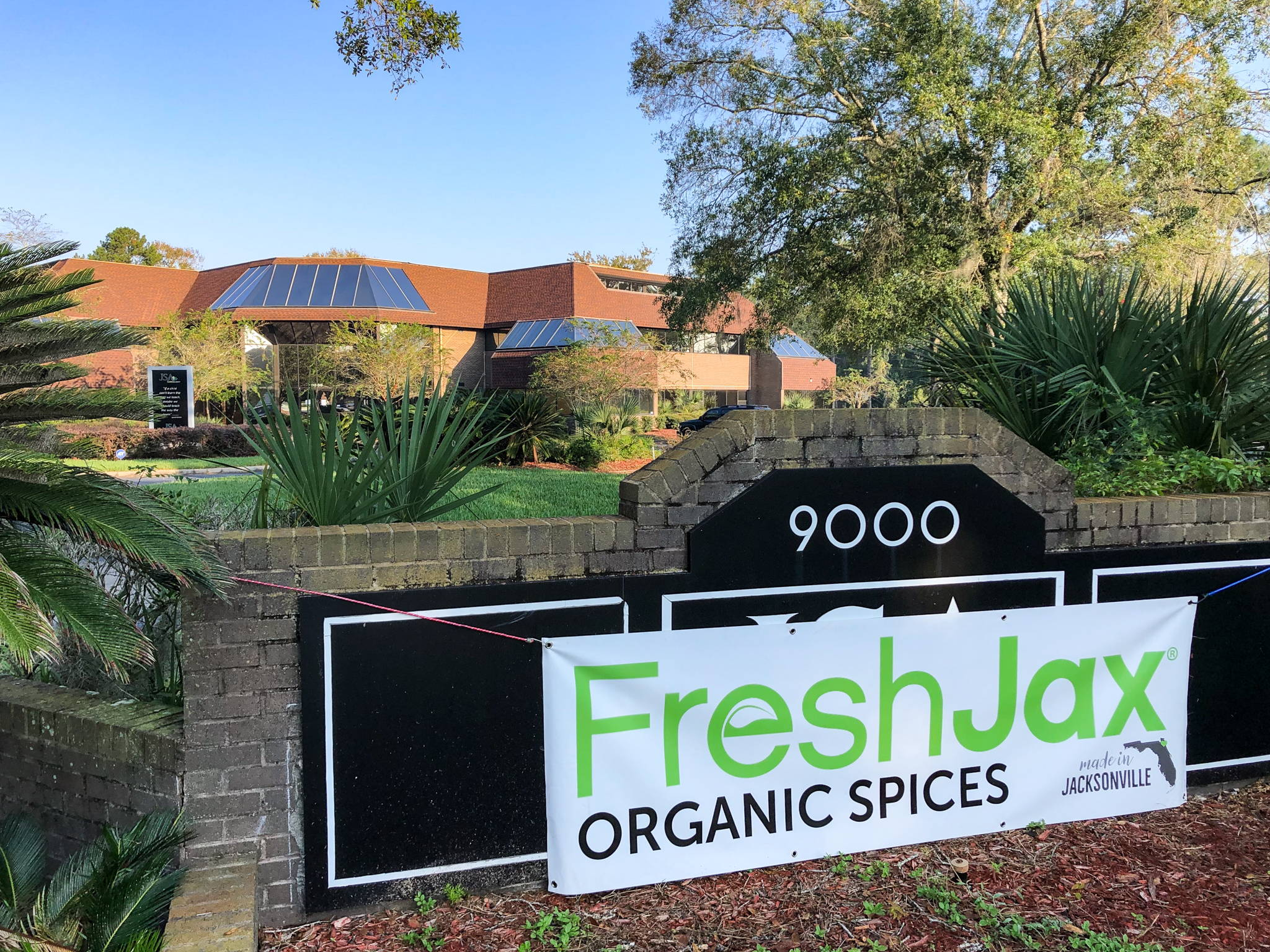 FreshJax Organic Spices sign hanging in front of new building