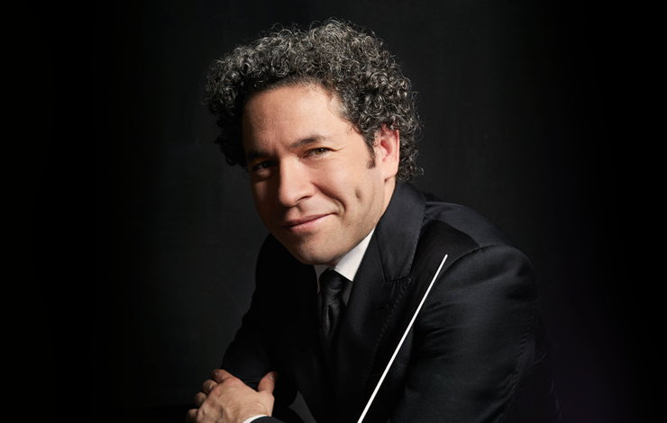 a portrait of Gustavo Dudamel, smiling and holding a conductor's stick