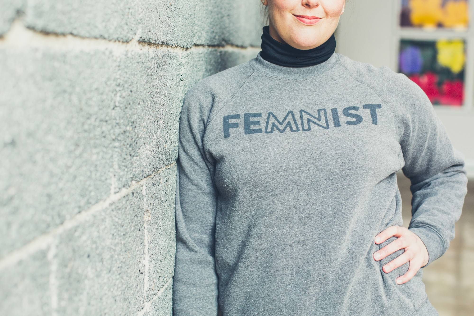 "Photo of a white woman wearing a grey crewneck sweatshirt. ""FeMNist"" is printed on the sweatshirt in black print."