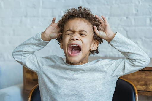 A child with his hands on his head, screaming out in frustration - Photo by Keira Burton from Pexels