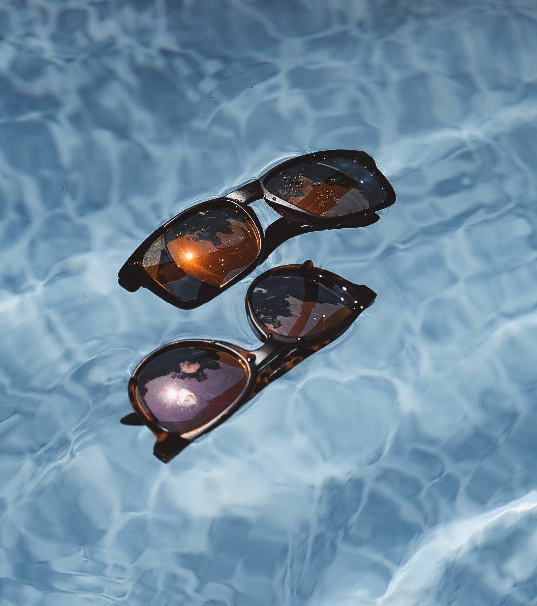 Two pairs of Rheos sunglasses float perfectly in the water.