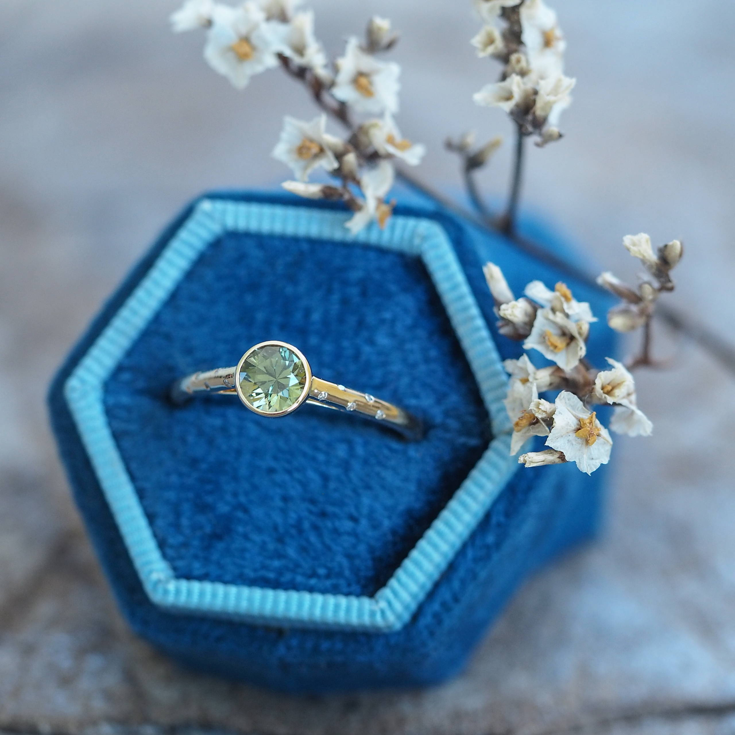 A custom made ethical gold sapphire ring featuring an ethically sourced sapphire from Borneo and conflict free diamonds.