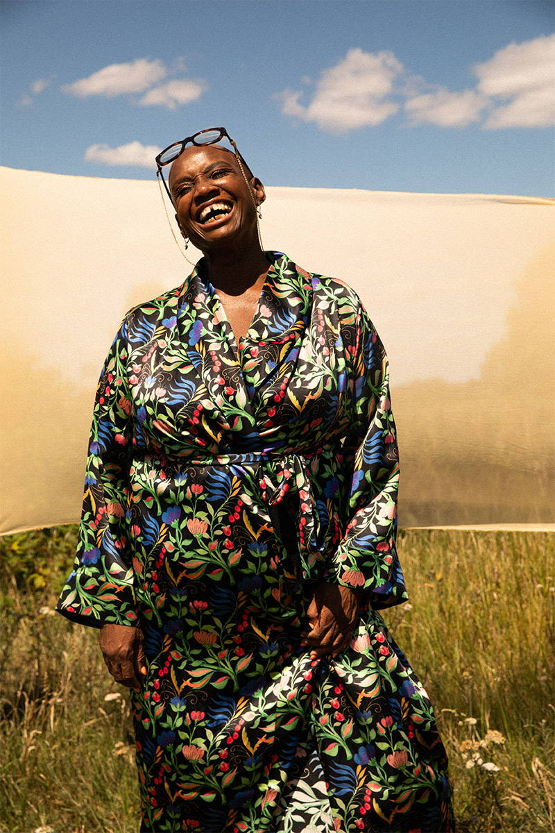 Andi Oliver wearing YOLKE Anais Black silk Gown standing in a field with a yellow silk flying behind her