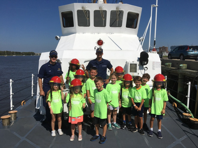 students on boat with Coast Guard officers