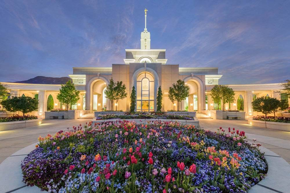 LDS art photo of the Mount Timpanogos temple and circular flowerbed against a purple sky.