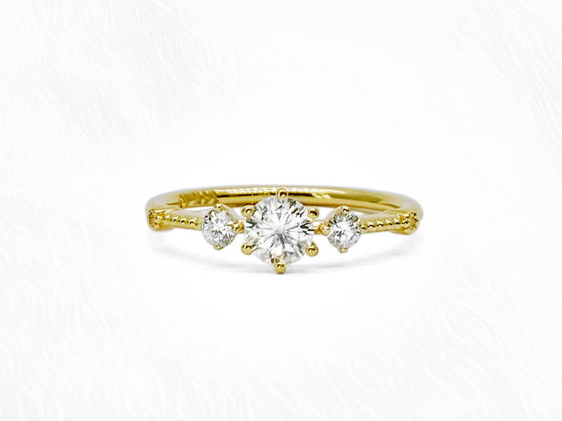 Yellow gold engagement ring with central round diamond and two small side diamonds.