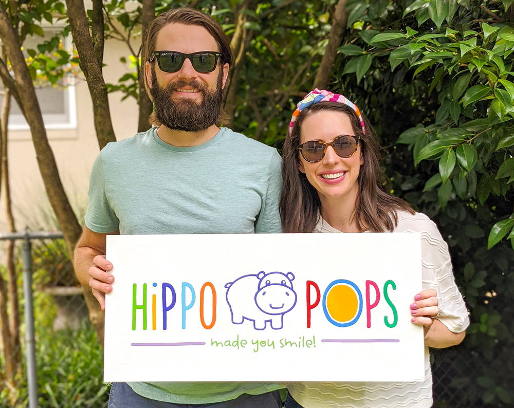 Photo of HippoPops owners Alex and Bess holding HippoPops sign