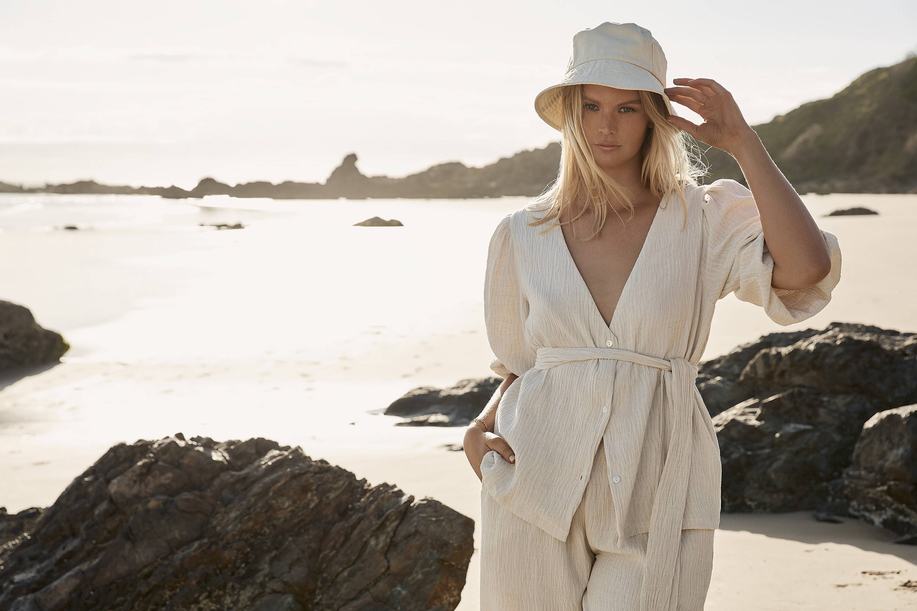 beautiful blonde woman not smiling touching hat wearing loose natural linen top and pants with a tie at waist sand and rocks in background