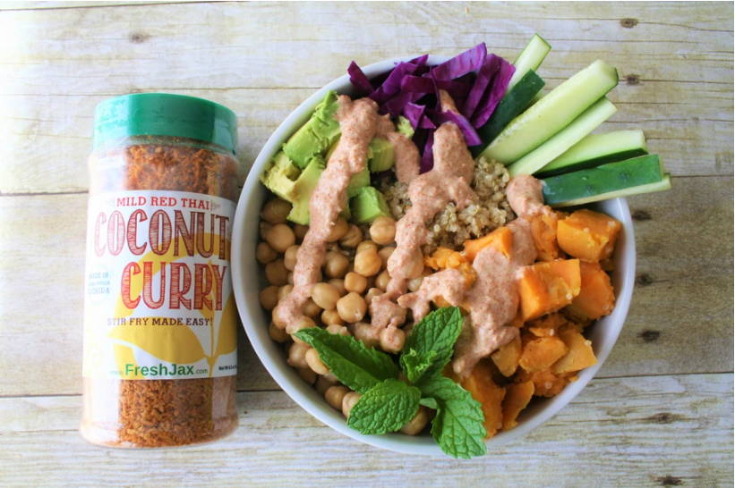 A bottle of FreshJax Organic Coconut Curry Mild Red Spice along side a red coconut curry buddha bowl.