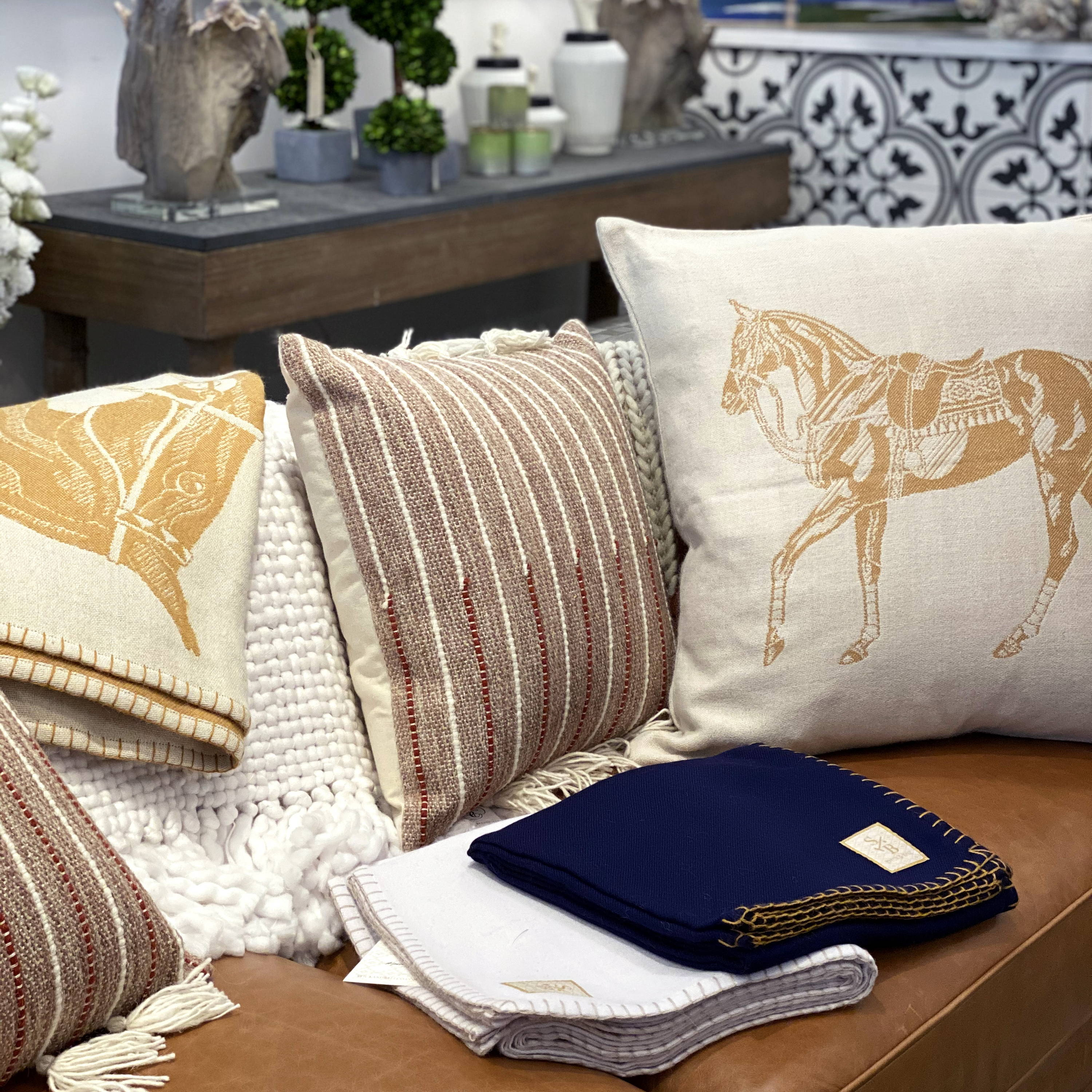 Display of sustainable alpaca home decor - Polo Pony pillow & throw blankets - Stick & Ball