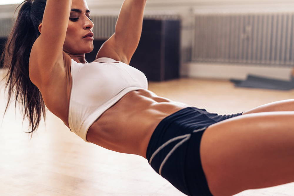 woman doing core ab exercises with concentrated expression