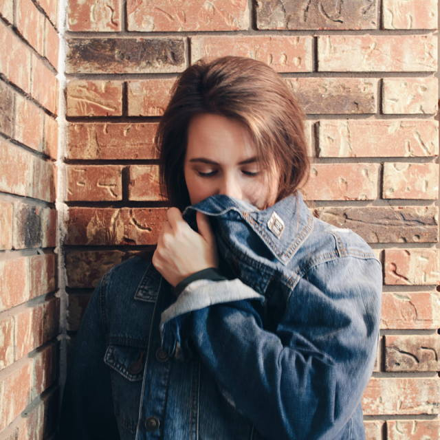 Brunette girl against a red brick wall wearing a jean jacket with enamel pins