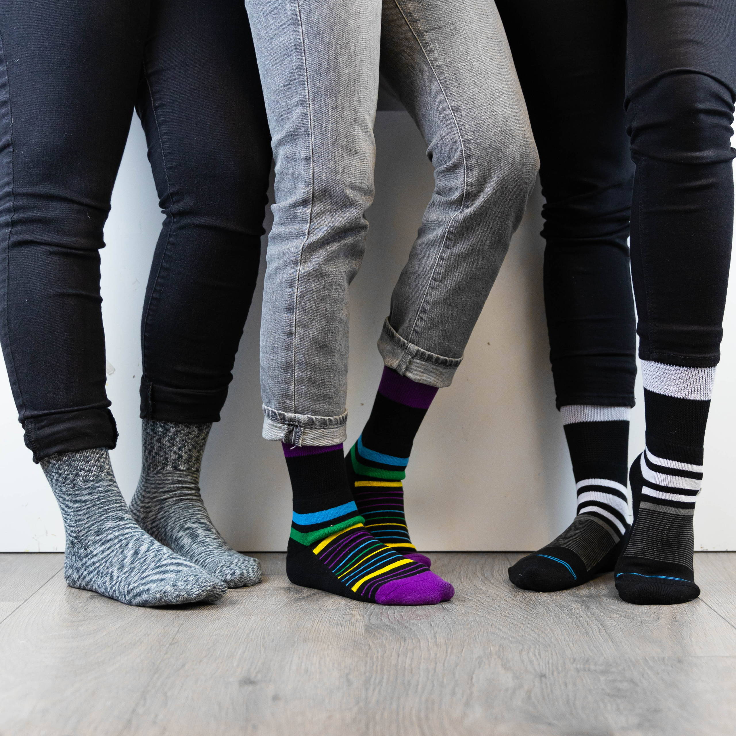 Three people standing next to eachother, all wearing Dr. Segal's diabetic socks.
