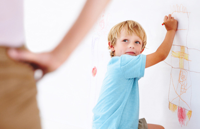 child drawing on wall