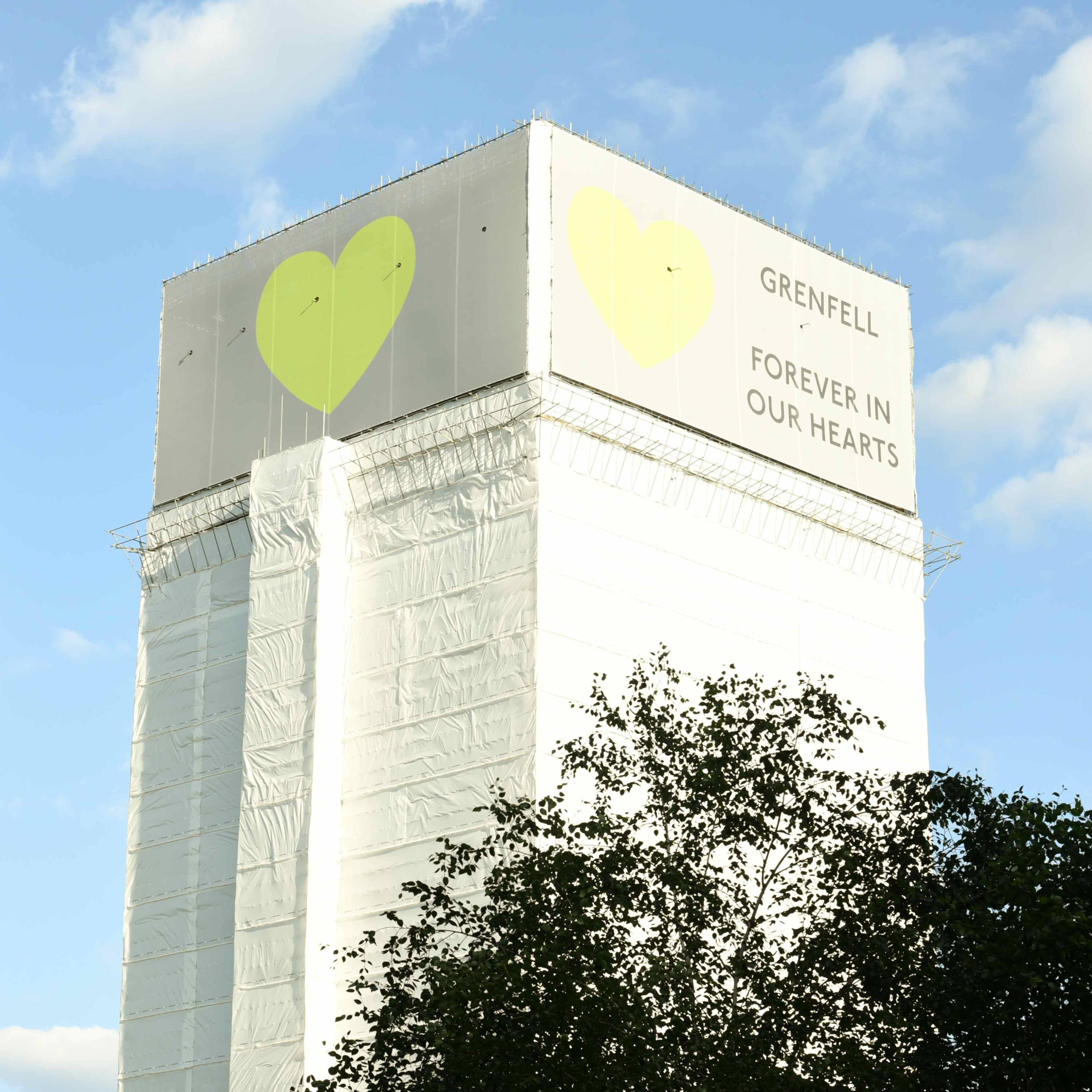 Grenfell Tower with sign reading: forever in our hearts