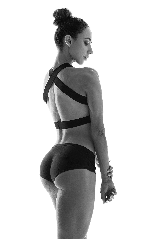 Back view of toned young woman in a black bikini