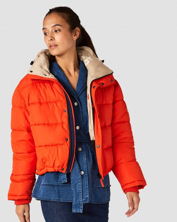 Woman wearing red recycled polyester insulated winter jacket from Kings of Indigo