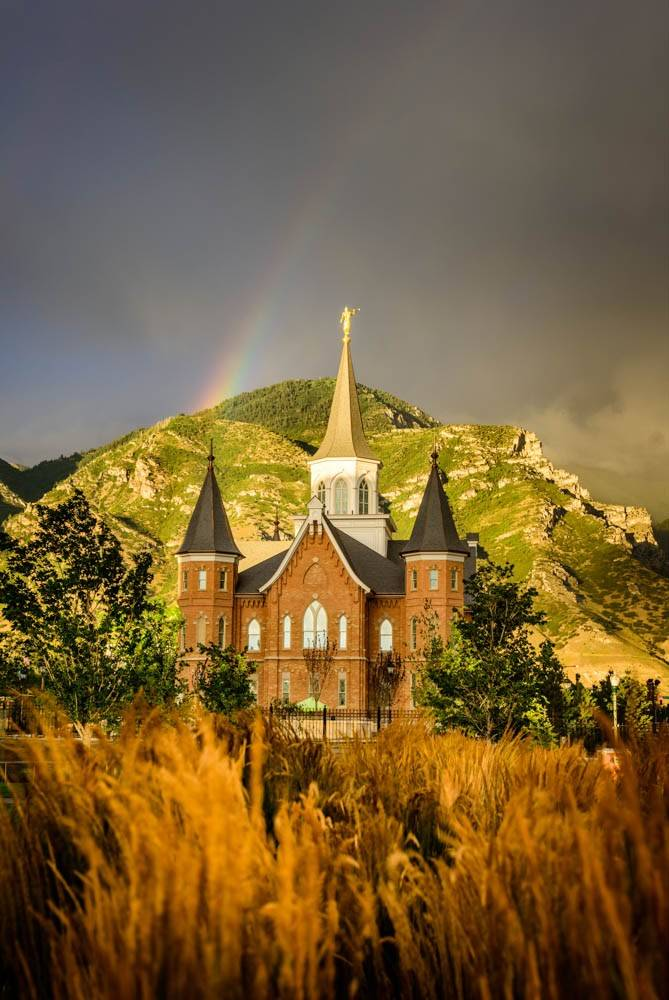 Vertical photo of the Provo City Center Utah LDS Temple against the backdrop of mountains, dark clouds, and the start of a rainbow.
