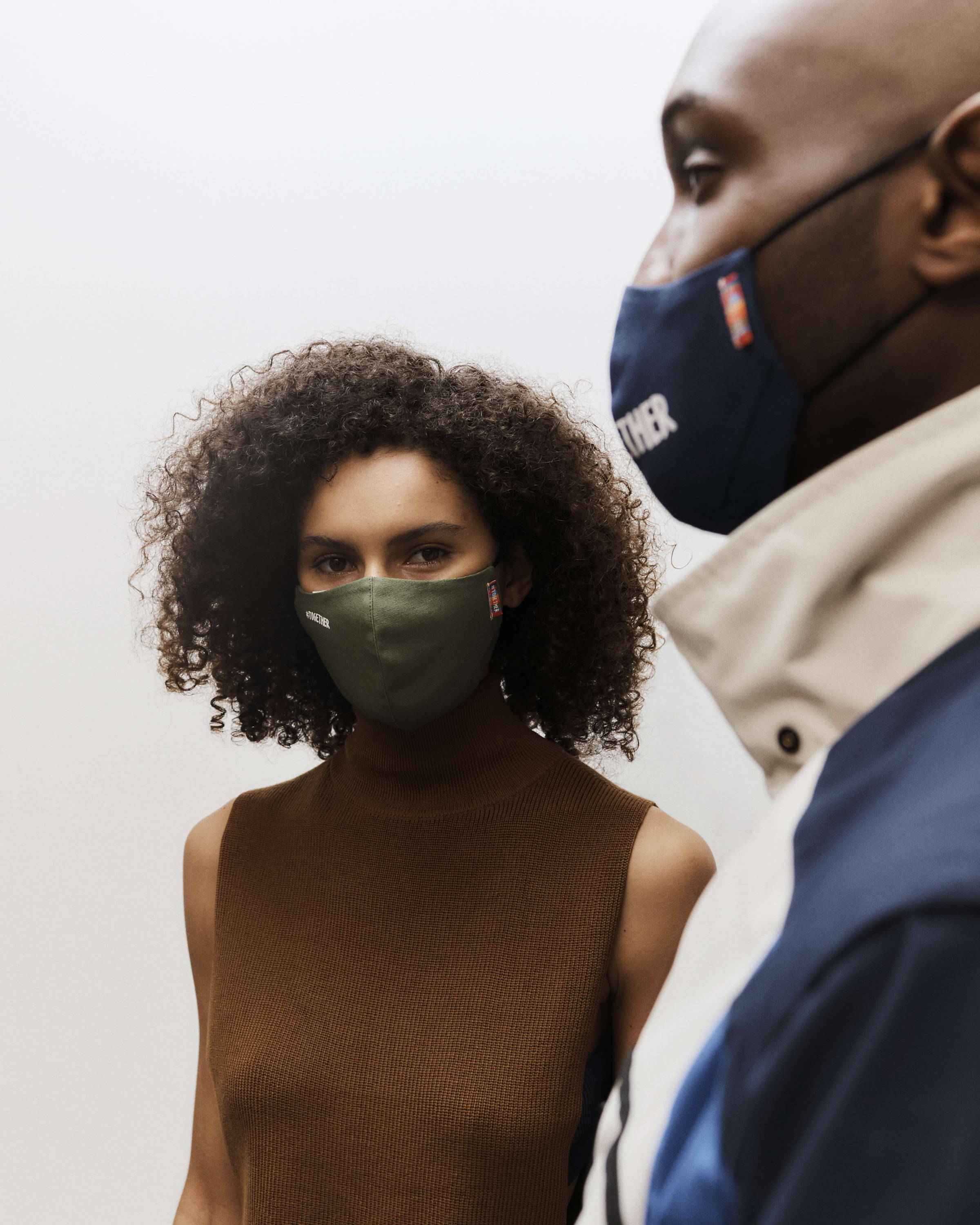 A man and a woman model wear olive green and navy blue organic cotton face masks