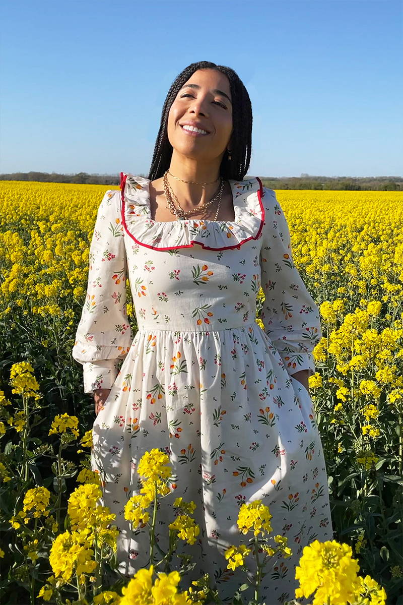 YOLKE's Tulip print Beatrice Dress with a red trimmed frill in a field of yellow flowers