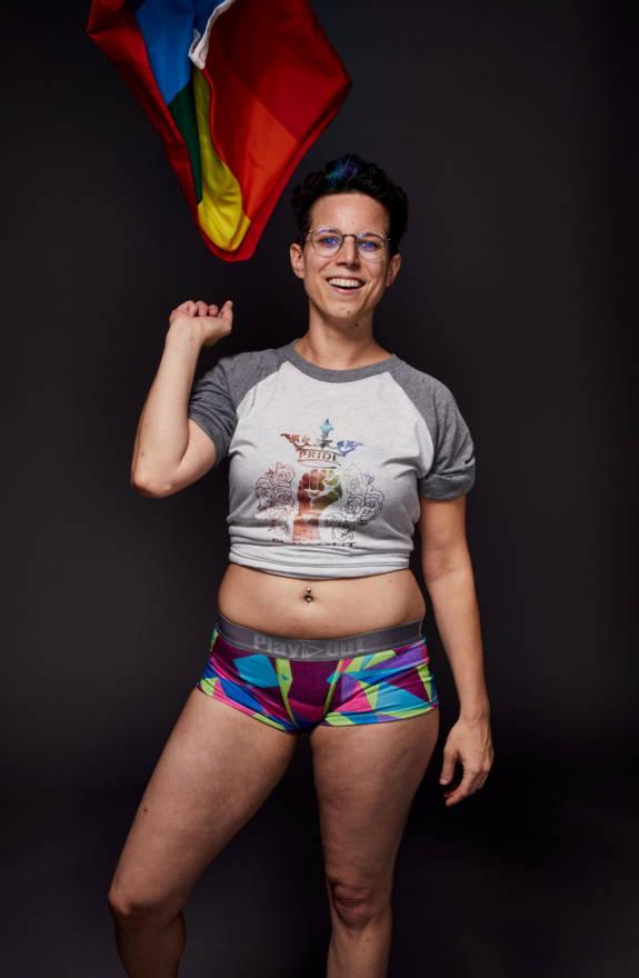 Female model wears LGBTQ Pride shirt and geometric multi-colored print boxer briefs underwear.
