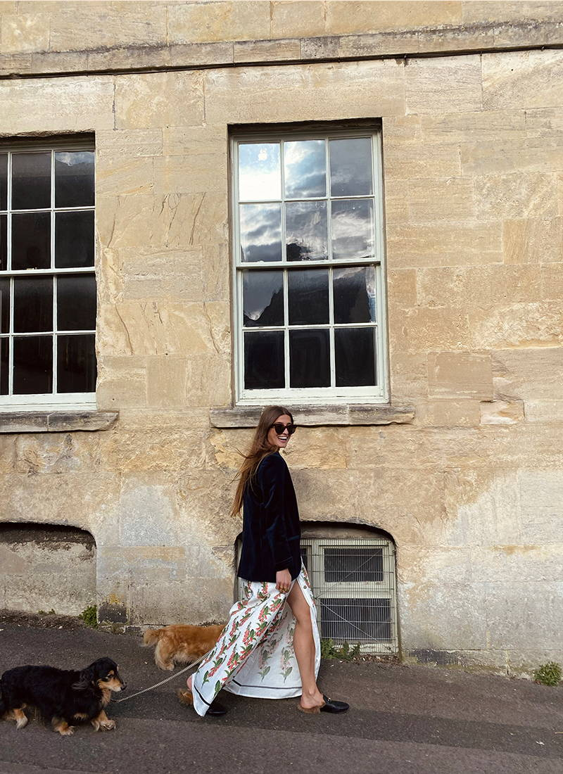 Rowan walking along with her dog in in foxglove print Valentina linen dress