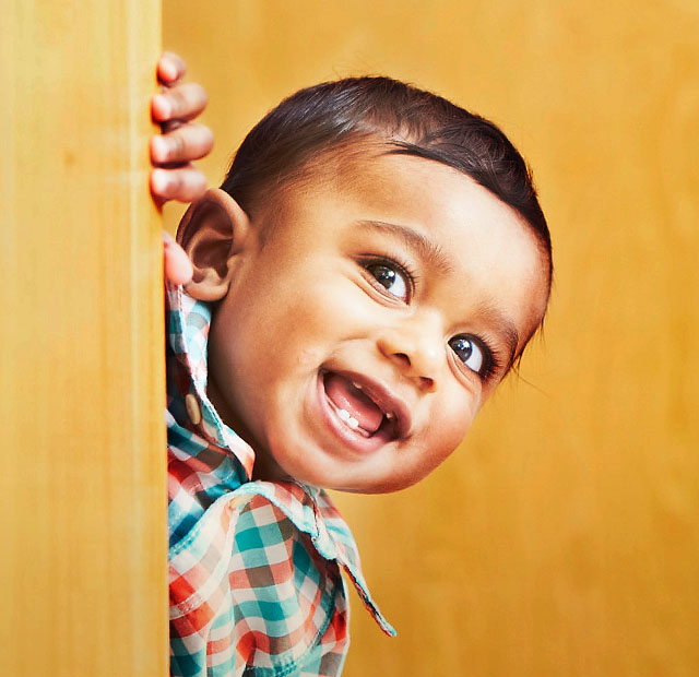 Young infant peeking around a corner and smiling