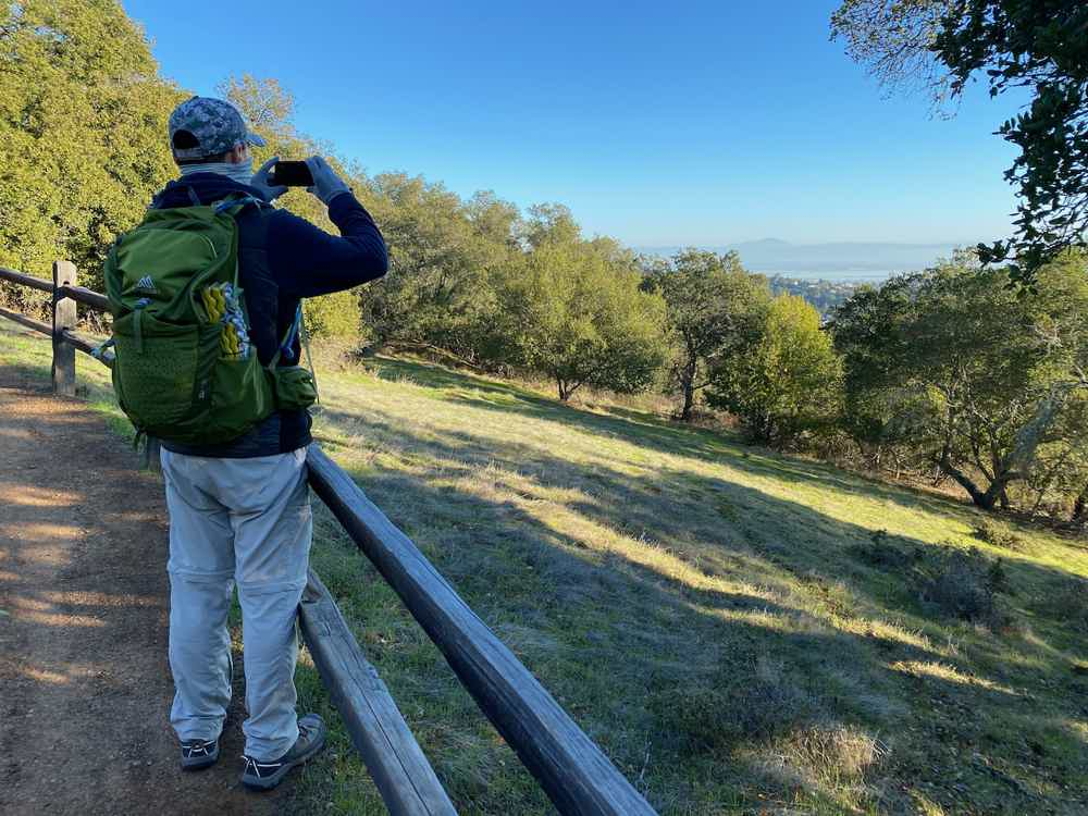 Hiker taking a photo of the view from Edgewood Park and Natural Preserve in Woodside
