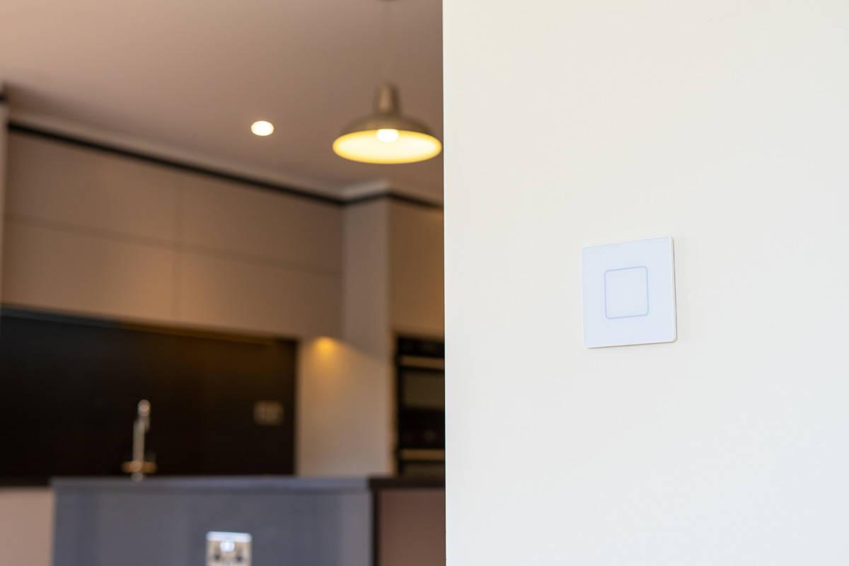 Faradite Einzelgang-TAP-Lichtschalter in mattweiß auf einer Küchenwand.