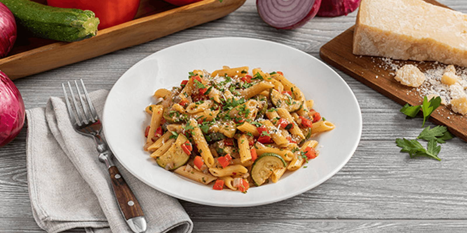 Bowl of pasta with chopped vegetables on a counter surrounded with vegetables and cheese.