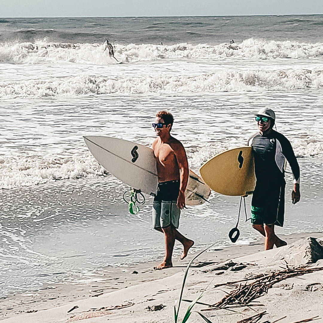 Two surfing buddies walk along the shore, wearing their Rheos sunglasses.