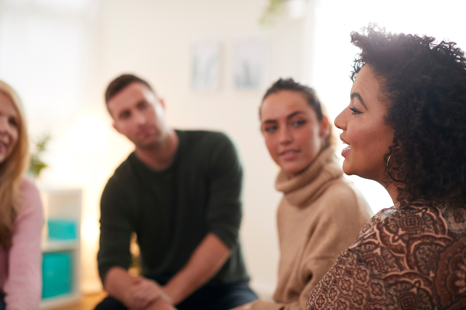 Photo of a dark skinned woman talking in a therapy circle smiling.