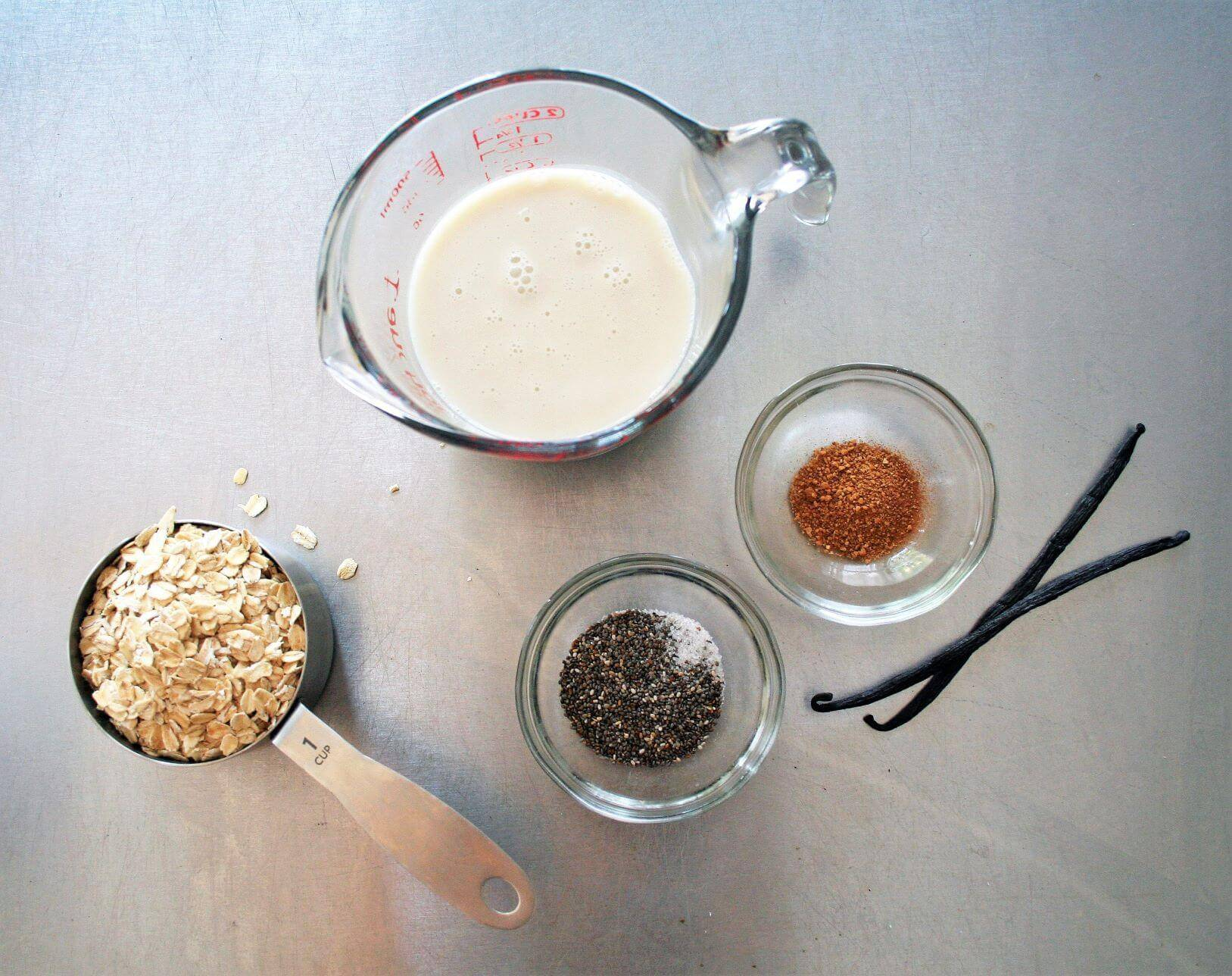 Oats in measuring cup, almond milk, chia seeds, FreshJax Organic maple Cinnamon, and vanilla beans on table.