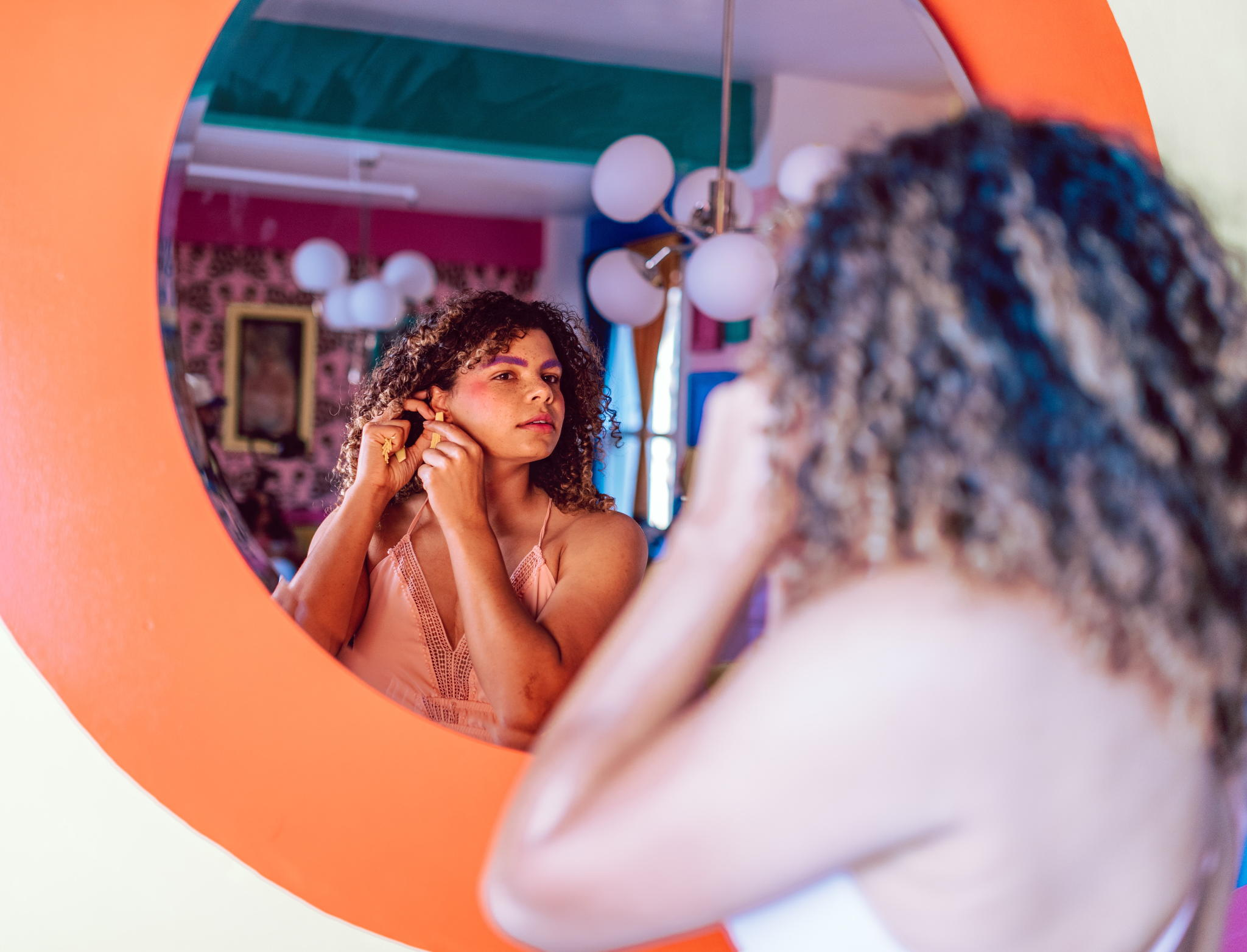 A beautiful mixed woman with curly hair looks at herself in the mirror while putting on an earring.