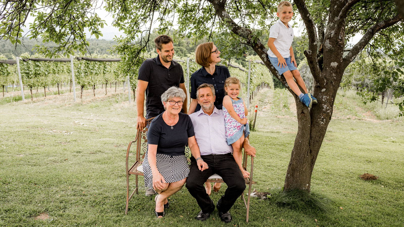 3 Generationen der Familie Trummer auf einer Bank vor dem Weingarten. Ein Bub sitzt im Baum.