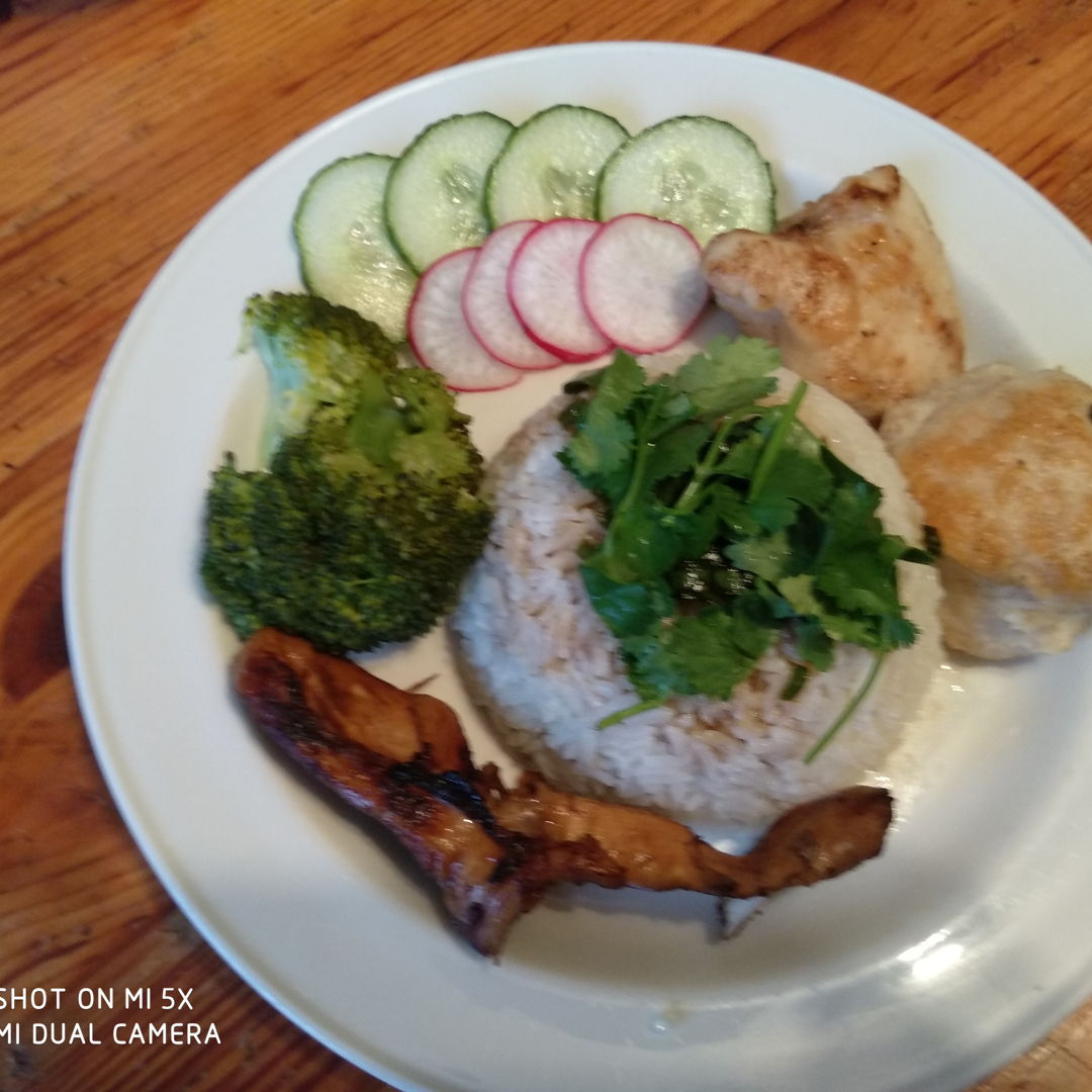 Roasted chicken rice with steamed broccoli garnished with fresh coriander, cucumber and radish slices. Served with ginger sauce and chilli sauce.