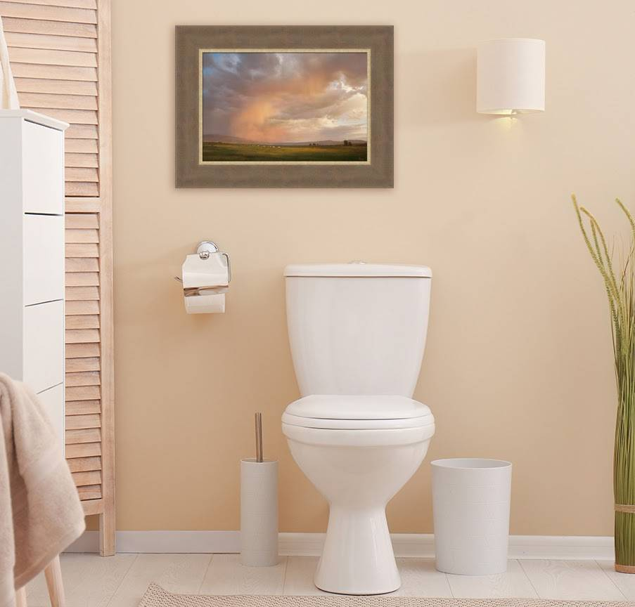 LDS art painting of a beautiful sky with pioneers crossing the plains. It is hung on tan-colored bathroom wall above the toilet.