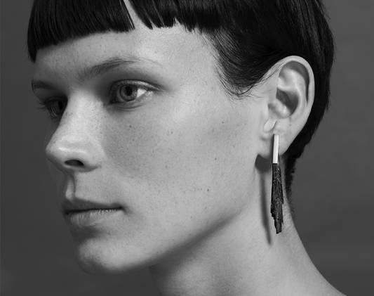 a woman wears a pair of earrings