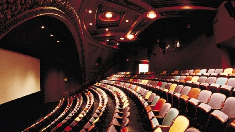 A cinema auditorium with an ornate arch and multi-coloured seats.