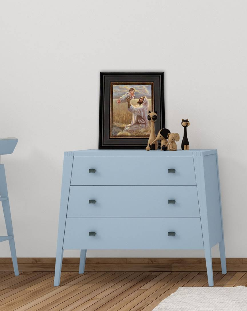 A small art painting of Jesus playing with a small child. The painting is placed on top of a child's dresser.