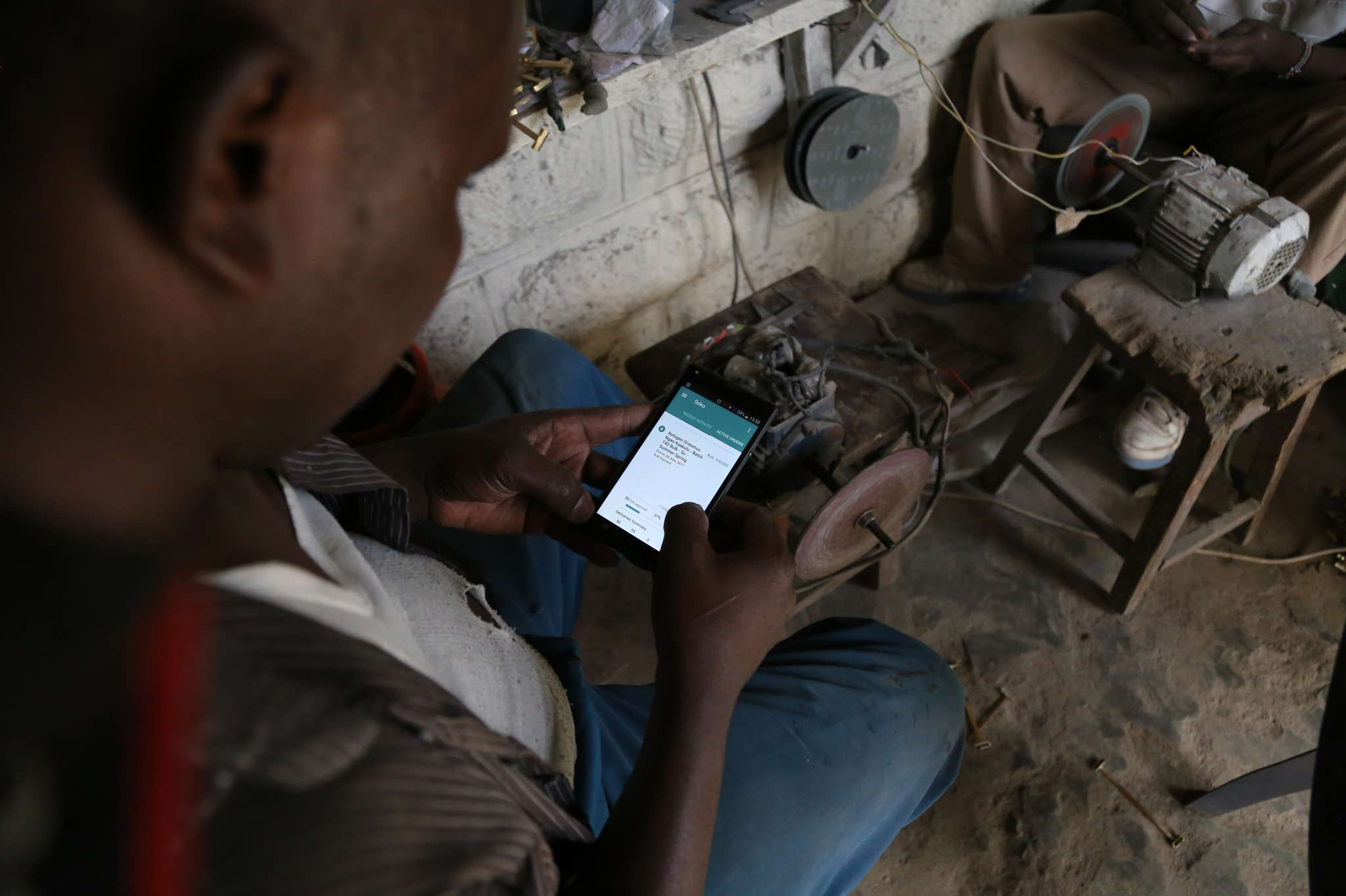 One of SOKO's artisan partners, Onesmus Ngao, reviews his work order on our proprietary mobile app.