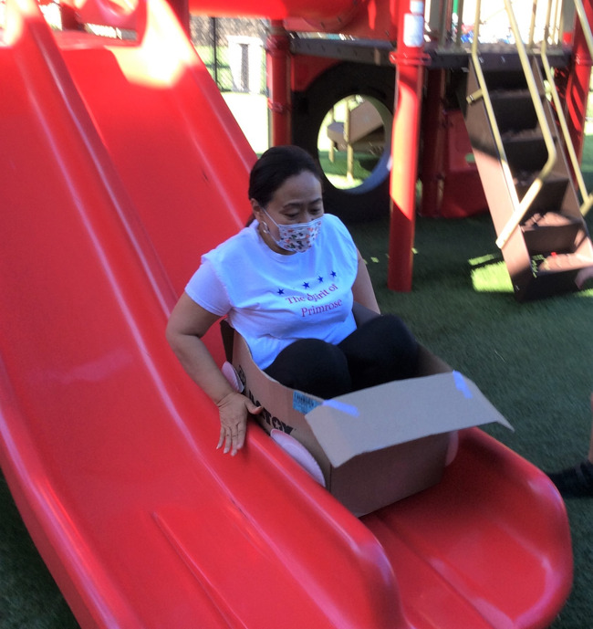 Ms.Pearl sliding down the playground slide in a boxcar made by the summer adventure club students