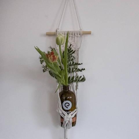 Eine Flasche von Rho Kombucha wird als Vase für Blumen verwendet und hängt an einen Seil an der Wand.