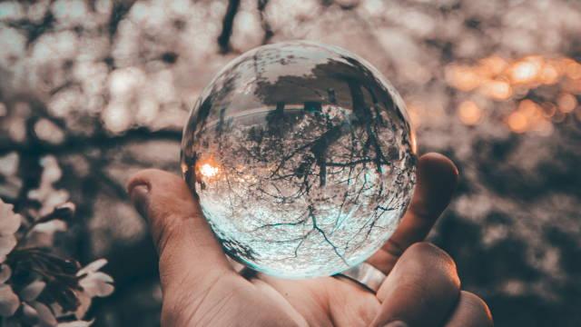 En person, som ser igennem en glaskugle, hvor landskabet er helt forvrænget. Det er lidt det samme med bias.